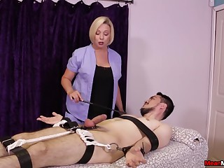 Strict blonde masseuse gives a Femdom handjob to a bound client
